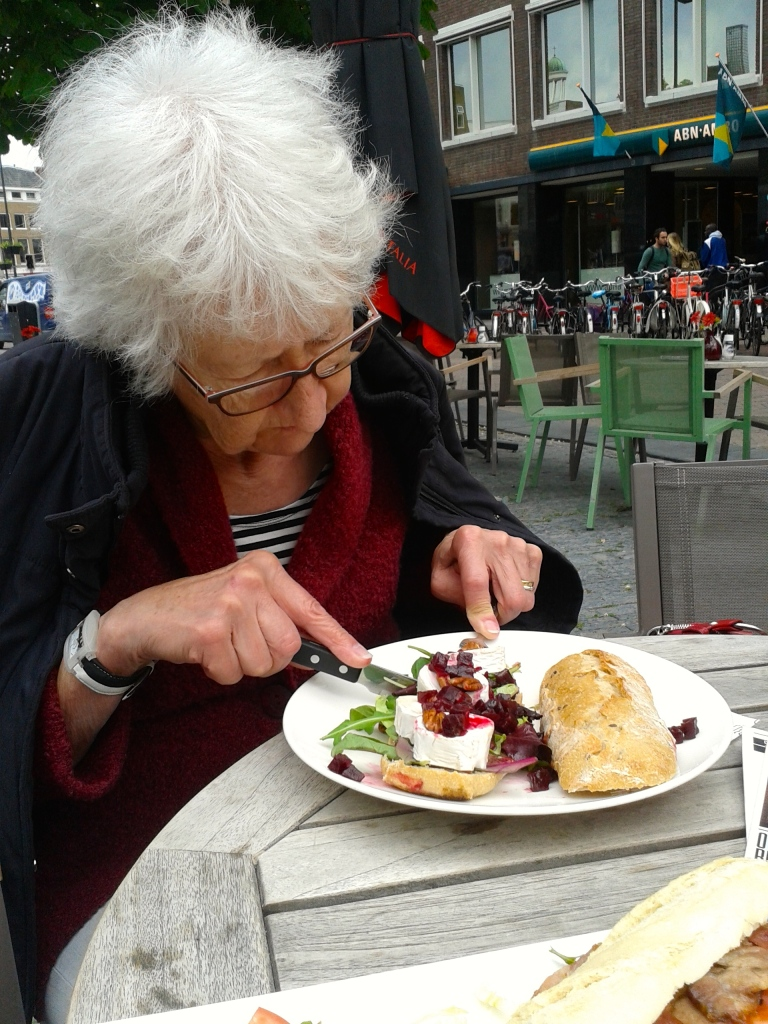 My grandmother eating a goatcheese sandwich with beets, honey and nuts at De Beurs, Utrecht.